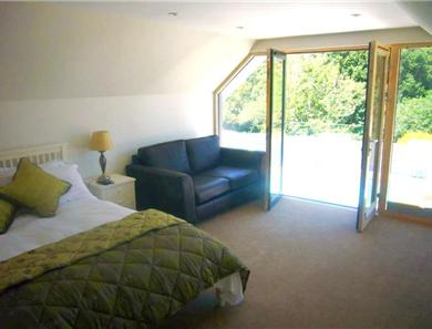 The spacious master bedroom has views over the pool area and the sea.