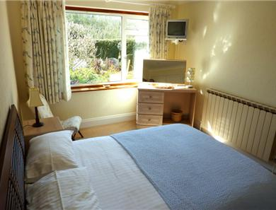 The bedroom has a lovely picture window overlooking the garden.